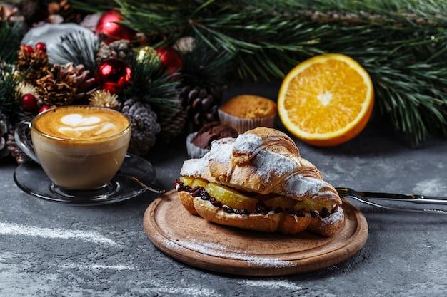 クロワッサンと新年の朝食。チョコレートと焼きオレンジの新年のクロワッサン。 Premium写真
