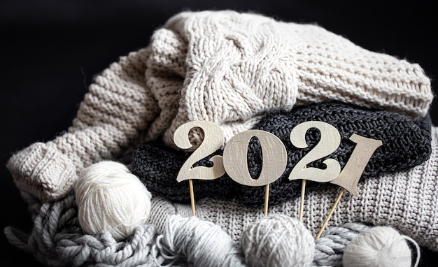 New year's composition with knitted items and wooden new years number on a dark background close up. Free Photo