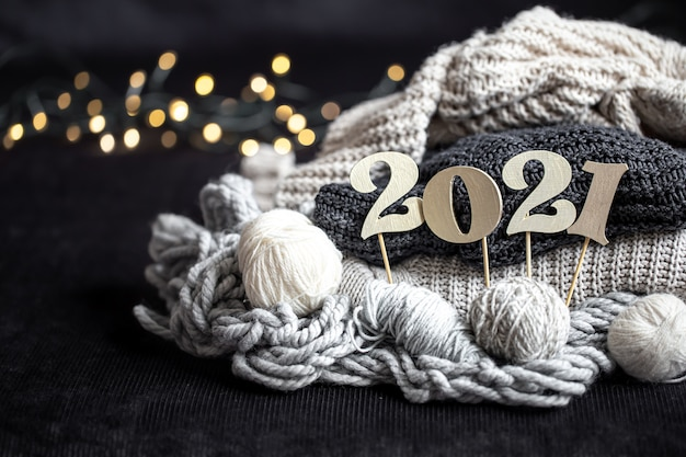 New year's composition with knitted items and wooden new years number on a dark background. Free Photo
