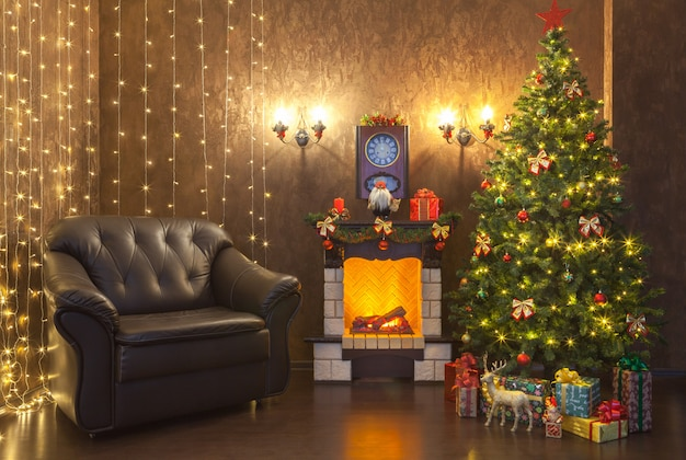 New year's decoration of the interior of the living room with a fireplace and a leather armchair. Premium Photo