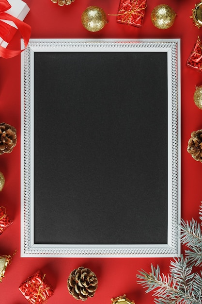 New year's frame with new year's toys, fir branches and gifts in an environment on a red background. greeting card with christmas, new year with free space for greeting texts. Premium Photo