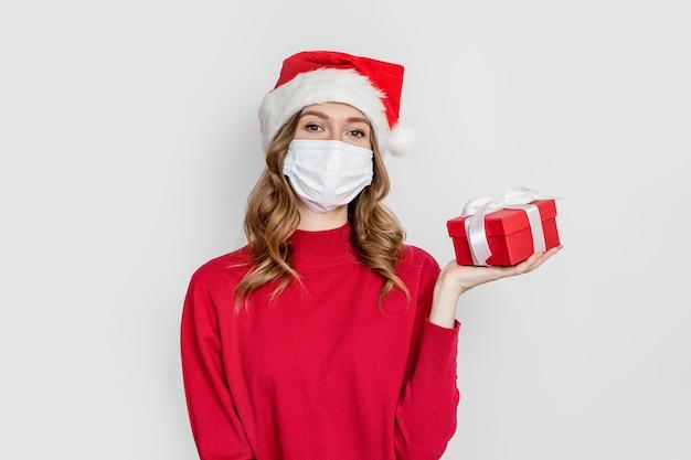 コロナウイルス検疫パンデミック中の2021年の新年の贈り物。医療マスクとサンタの帽子をかぶった赤いセーターの女子学生は、白いスタジオの背景に分離されたギフトボックスを保持します。 Premium写真
