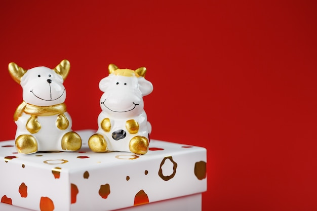 New year's toy of a bull and a cow with a gift on a red background. Premium Photo