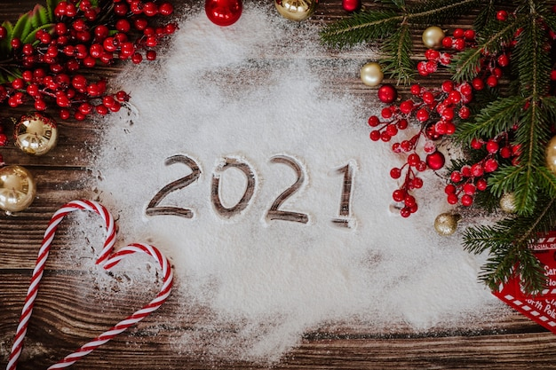 New year template with christmas tree decorations, balls, letter, sweets, flour and red berries on a wooden textured surface. view from above. Premium Photo