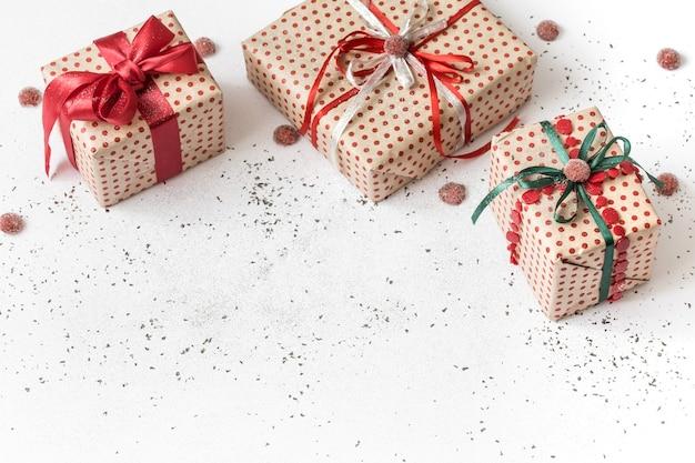 Parete festiva bianca di nuovo anno con regalo legato con nastro rosso. Foto Gratuite