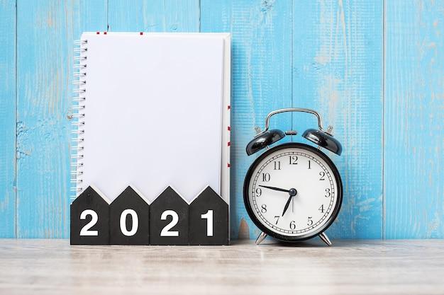 Новый год с пустой записной книжкой, будильником и деревянным номером Premium Фотографии