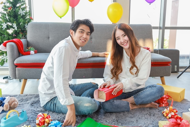 New year and xmas holiday concept. portrait of smiling asian man woman make a gift box and decorate living room for christmas party. Premium Photo