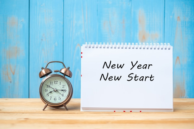 New years new start text on notebook and retro alarm clock Premium Photo