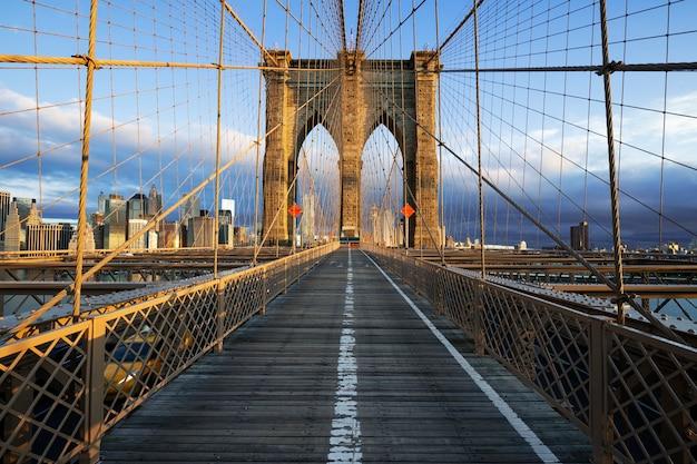 マンハッタンのニューヨーク市ブルックリン橋のクローズアップ。高層ビルとハドソン川の街並み。 無料写真