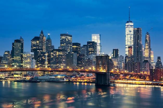 ブルックリン橋のある夕暮れ時のニューヨーク市マンハッタンのミッドタウン。米国。 無料写真
