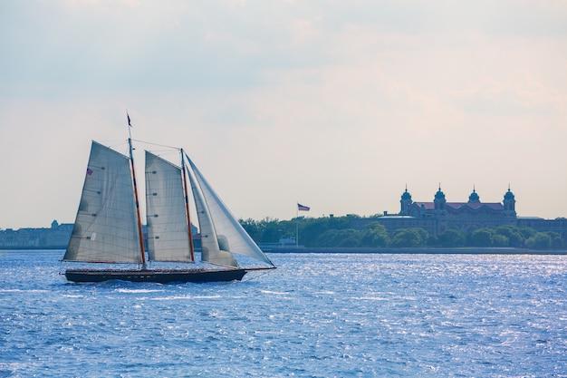 New york sailboat sunset and ellis island Premium Photo