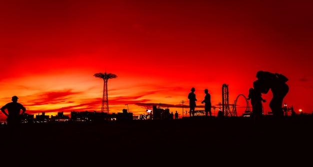 Нью-йорк, сша - 22 сентября 2017: пляж кони-айленд в нью-йорке. силуэты людей и вышка для прыжков с парашютом на фоне заката Premium Фотографии