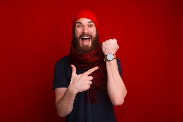 Фотография счастливого бородатого парня, указывающего на его часы newa и задержанного на встрече Premium Фотографии