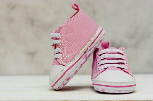 Закройте вверх по розовым тапкам ребёнка, ботинки спорта закрывают вверх по newbord, материнству, концепции беременности с космосом экземпляра. Premium Фотографии