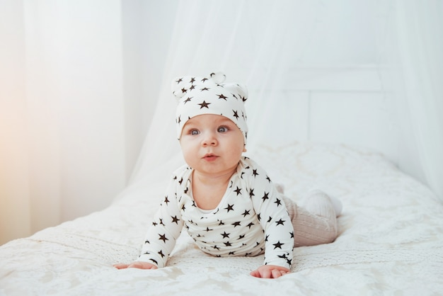 Newborn baby dressed in a white suit and black stars is a white soft bed in the studio Premium Photo