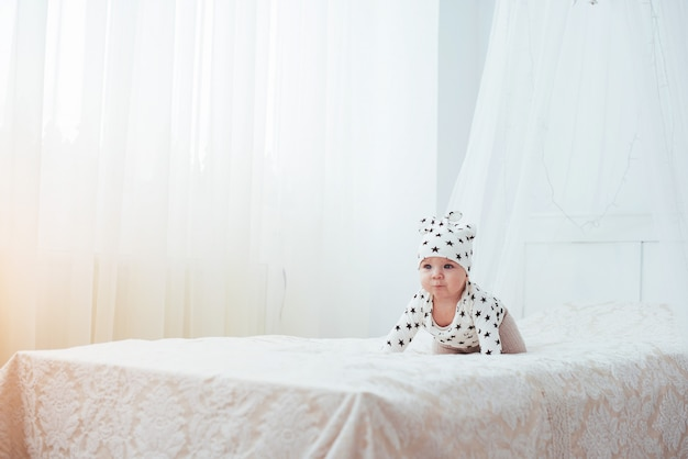 Newborn baby dressed in a white suit and black stars is a white soft bed Premium Photo