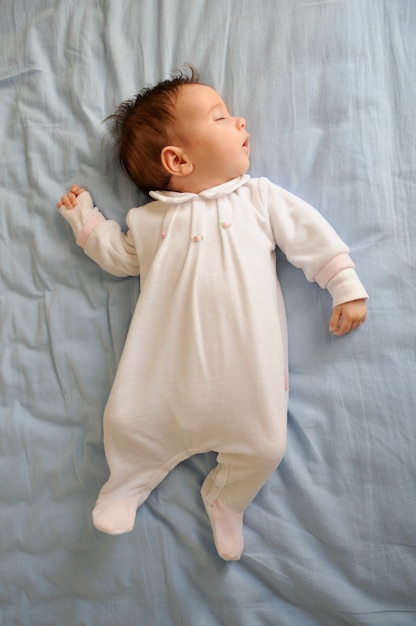 Newborn baby girl sleeping on blue sheets at home Free Photo