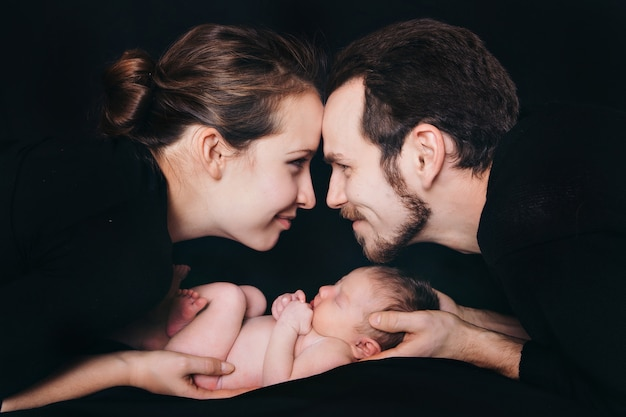 Newborn baby lying on the hands of parents on a black background. imitation of a baby in the womb. Premium Photo