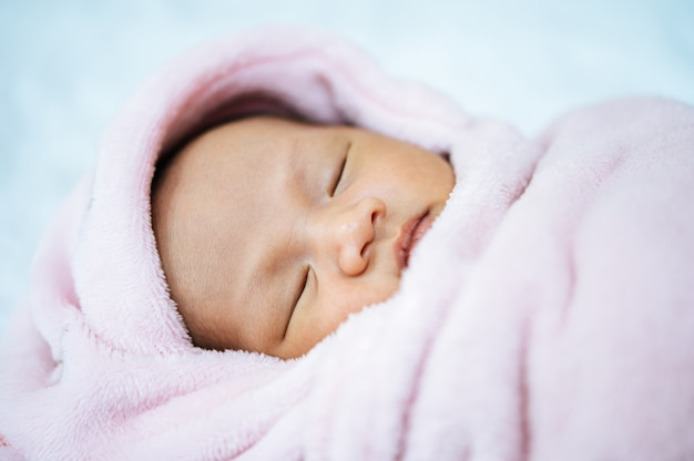 Newborn baby sleeping on a soft pink blanket Free Photo