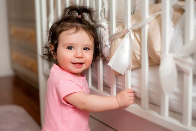 Newborn baby toddler girl in baby bed Premium Photo