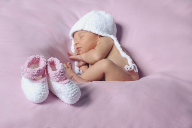 Newborn baby in white knitted hat and a pair of baby white and pink shoes Premium Photo