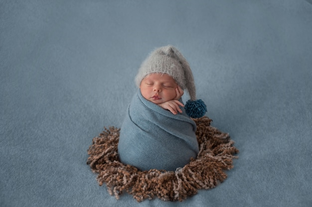 Newborn baby with white beret and wrapped with blue shawl. Free Photo