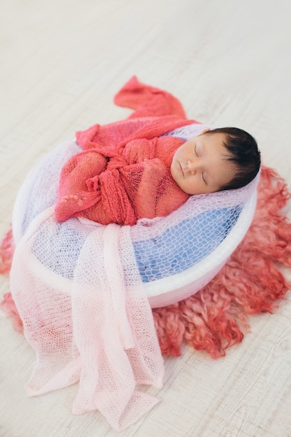 Newborn baby wrapped in a blanket sleeping in a basket. concept of childhood, healthcare, ivf Premium Photo