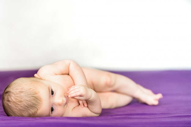 Newborn blonde baby 3 months old lying on her stomach and head raised Premium Photo