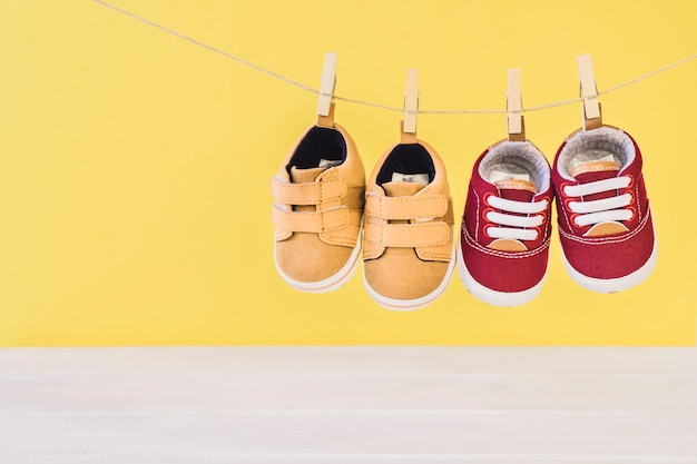 Newborn concept with two shoes on clothesline Free Photo