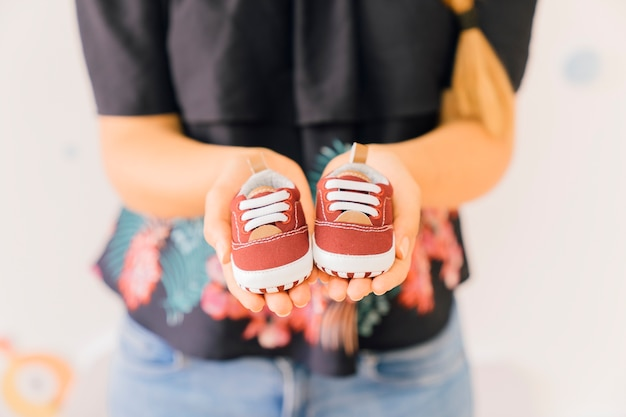 Newborn concept with woman showing shoes Free Photo