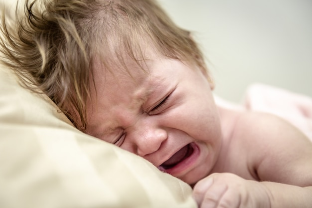 Newborn crying baby girl. new born child tired and hungry in bed. children cry. bedding for kids. infant screaming. Premium Photo