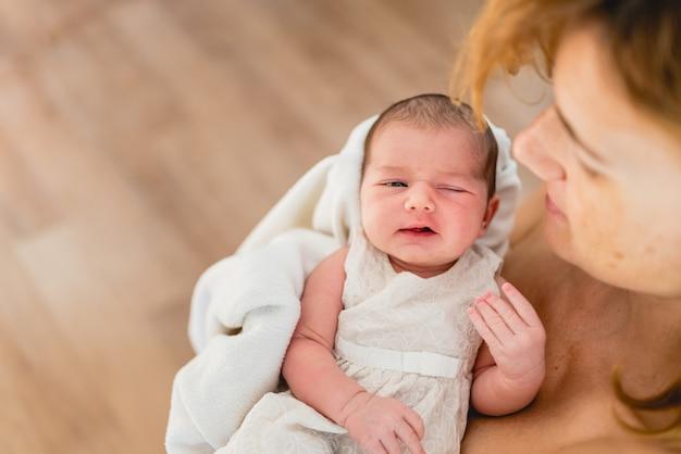 彼女の母親の腕を愛するで生まれたばかりの女の子 Premium写真
