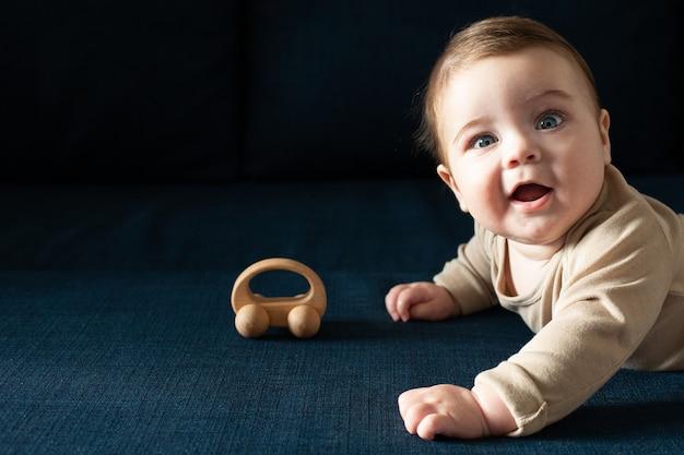 베이지 색 Bodysuit에서 신생아 유아 소년 나무 장난감 측면보기와 함께 재생 프리미엄 사진