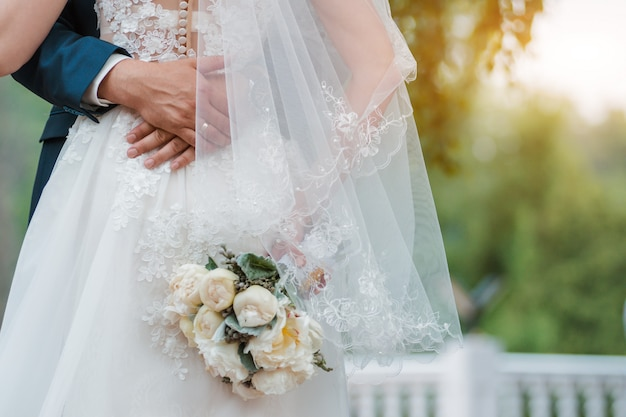 Newly married couple. wedding day. bouquet of the bride in the hands, the groom's embrace. Premium P