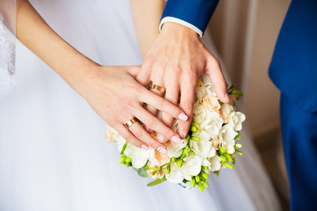 A newly weding couple place their hands on a wedding bouquet showing their wedding rings. Premium Photo