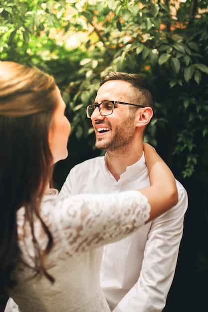 新婚カップルがお互いを見て、結婚式の日に笑顔します。愛の概念。 Premium写真