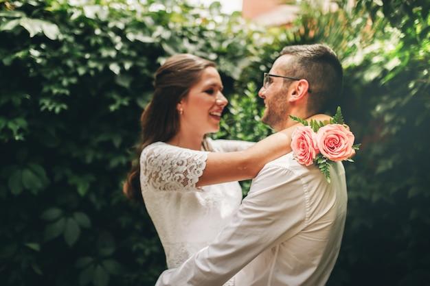 新婚カップルがお互いにハグダンスを見て、結婚式の日に笑顔。連合と愛の概念。 Premium写真