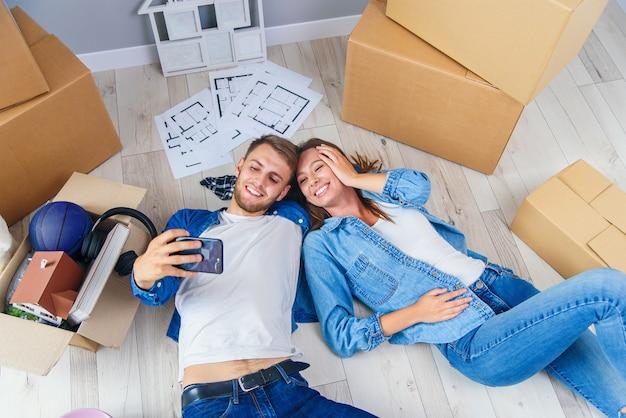 新婚カップルは彼らの新しいアパートの木の床に横たわって、スマートフォンでselfieを作ります。上面図。 Premium写真