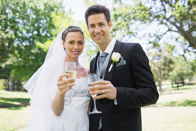 Newlywed couple toasting champagne in park Premium Photo