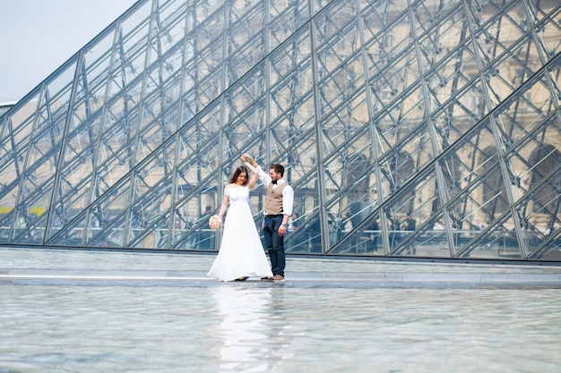 Newlyweds dancing in front of louvre museum Premium Photo