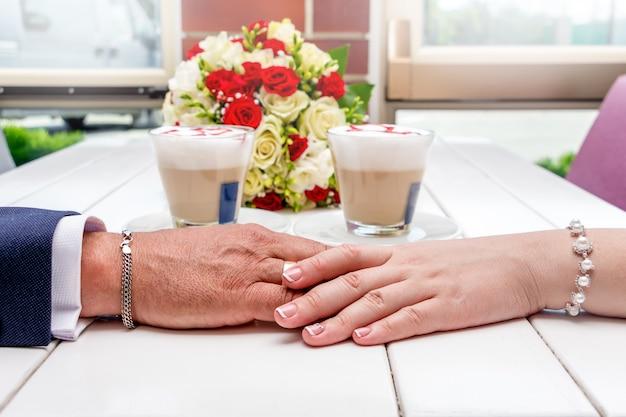 Молодожены держатся за руки. руки молодоженов, кофе и свадебный букет на белом столе. молодожены в кафе празднуют свадьбу Premium Фотографии