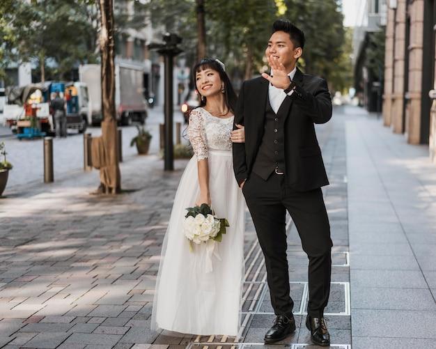 거리에서 함께 포즈를 취하는 신혼 부부 무료 사진