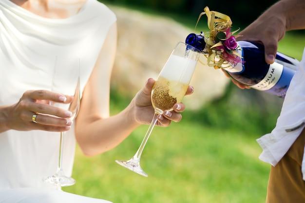 Newlyweds spill wine in glasses. Premium Photo