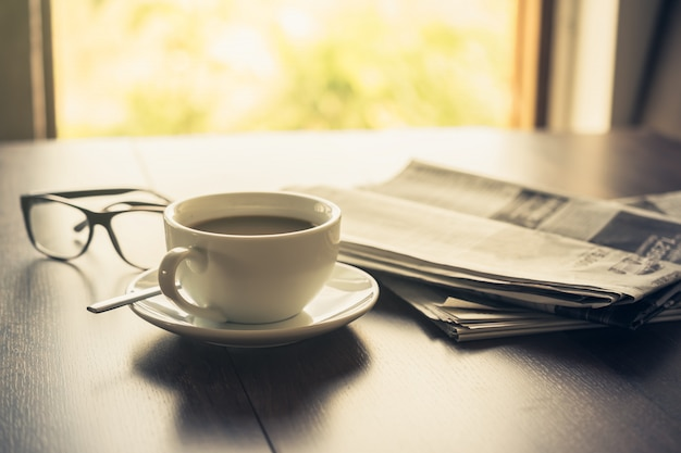 Newspaper reading glasses coffee cup and mobile phone on business desk business newspaper background . Premium Photo