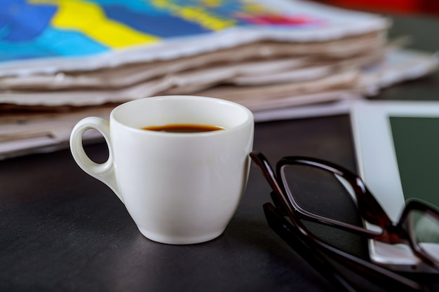 Newspapers and coffee cup, reading glasses and notepad Premium Photo