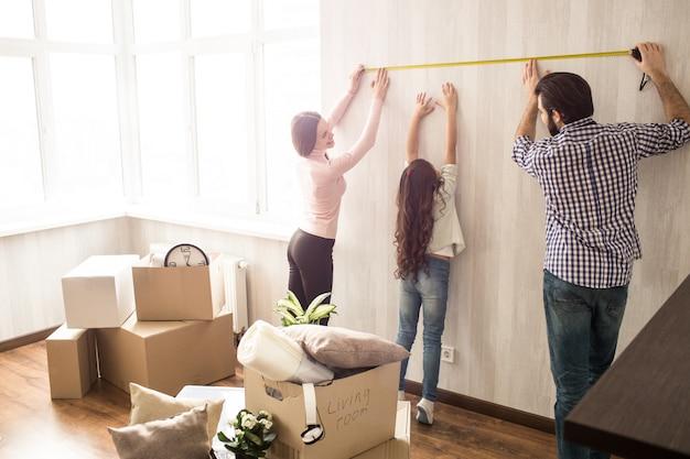 Хорошая и трудолюбивая семья работает вместе. мужчина и женщина измеряют длину стены, пока их дочь пытается помочь им. Premium Фотографии