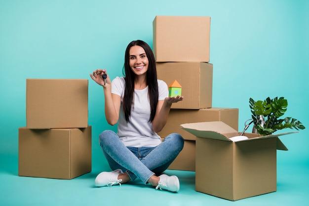 Симпатичная привлекательная жизнерадостная девушка, сидящая в позе лотоса с кучей коробок, держащая в руках фигуру дома Premium Фотографии