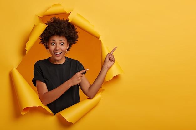 파삭 파삭 한 머리카락을 옆으로두고 광고를 보여주고 쾌활하고 호기심을 느끼는 멋진 매력적인 여성 모델 무료 사진