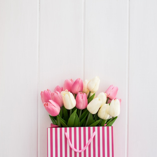 Nice bouquet of tulips inside a white and pink bag on a white wooden background Free Photo