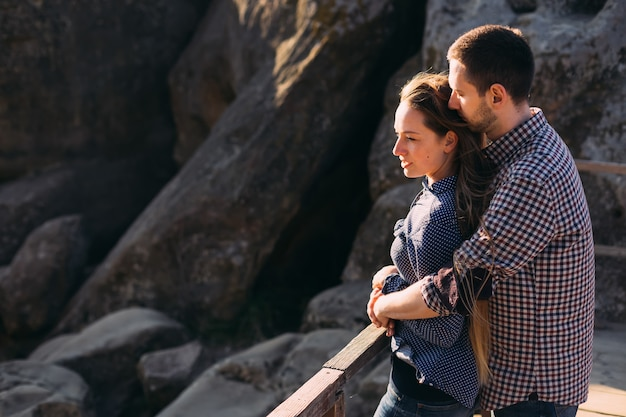 Nice couple hugging and enjoying a windy autumn day at rocks Premium Photo